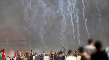 Pasukan Israel menembakkan gas air mata ke arah demonstran Palestina selama bentrokan di perbatasan jalur Gaza (11/5). Warga Palestina menggelar aski yang berujung bentrokan di perbatasan jalur Gaza. (AFP Photo/Mohammed Abed)