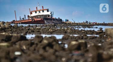 Warga memancing di atas sebuah kapal karam di pesisir Kali Adem, Muara Angke, Jakarta, Minggu (27/12/2020). Sebuah kapal yang telah karam selama bertahun-tahun tersebut dimanfaatkan oleh warga sebagai tempat memancing meskipun berisiko membahayakan keselamatan. (merdeka.com/Iqbal Nugroho)