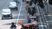 Delman hias membawa penumpang melintasi Jalan Medan Merdeka Barat, Jakarta, Selasa (19/6). Masa libur Lebaran 2018 dimanfaatkan sejumlah warga untuk berwisata di sekitar Monumen Nasional dengan menaiki delman hias. (Liputan6.com/Helmi Fithriansyah)