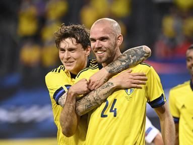 Pemain Swedia Marcus Danielson (tengah) merayakan dengan rekan setimnya Victor Lindelof setelah mencetak gol ke gawang Armenia pada pertandingan persahabatan jelang Euro 2020 di Solna, Swedia, Sabtu (5/6/2021). Swedia menang 3-1. (Jonathan NACKSTRAND/AFP)