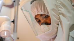"""Dr. Maureen P. Ines-Manzano, seorang dokter gigi, mengenakan setelan respirator dengan pemurni udara di dalam kliniknya di Manila, Filipina, pada 19 Oktober 2020. Pasien Dr. Manzano menjulukinya """"dokter gigi astronaut"""" karena mengenakan setelan PAPR utuk menghindari COVID-19. (Xinhua/Rouelle Umali)"""