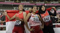 Pelari Indonesia, Putri Aulia, Ni Made Arianti, Endang Sari Sitorus, melakukan selebrasi usai menjuarai lari 100M T13 pada Asian Para Games di SUGBK, Jakarta, Rabu (10/10/2018). Indonesia meraih memborong tiga mendali. (Bola.com/M Iqbal Ichsan)