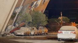 Sebuah bangunan miring karena pondasinya ambruk usai terjadi gempa di Hualien, Taiwan (7/2). Seorang pejabat dari divisi pemadam kebakaran setempat mengatakan bahwa orang-orang terjebak dalam bangunan di Hualien. (AFP Photo/Paul Yang)