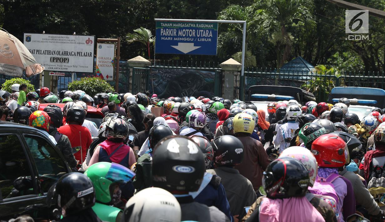 Warga memadati lajur pintu masuk area parkir motor kawasan Kebun Binatang Ragunan, Jakarta, Minggu (30/12). Libur panjang jelang pergantian tahun dimanfaatkan warga untuk berlibur di kawasan Kebun Binatang Ragunan. (Liputan6.com/Helmi Fithriansyah)