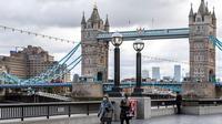 Orang-orang berjalan di tepi Sungai Thames di depan Tower Bridge, London, Inggris, pada 6 Oktober 2020. Inggris melaporkan 14.542 kasus terkonfirmasi baru COVID-19, menambah total infeksi di negara itu menjadi 530.113, menurut data resmi yang dirilis pada Selasa (6/10). (Xinhua/Han Yan)