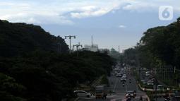 Kawasan gunung Gede-Pangrango terlihat samar menjadi latar belakang pemandangan di Jalan Benyamin Sueb, Kemayoran, Jakarta, Kamis (18/2/2021). Jika cuaca cerah, kawasan gunung Gede-Pangrango bisa terlihat dengan jelas dari atas jembatan layang Jalan HBR Motik. (Liputan6.com/Helmi Fithriansyah)