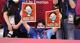 Seorang petugas mengacungkan poster yang menginstruksikan peraih medali untuk mengenakan kembali masker mereka saat seremoni penyerahan medali judo kelas 66kg putra Olimpiade Tokyo 2020, di Tokyo pada 25 Juli 2021. (AP Photo/David Goldman)