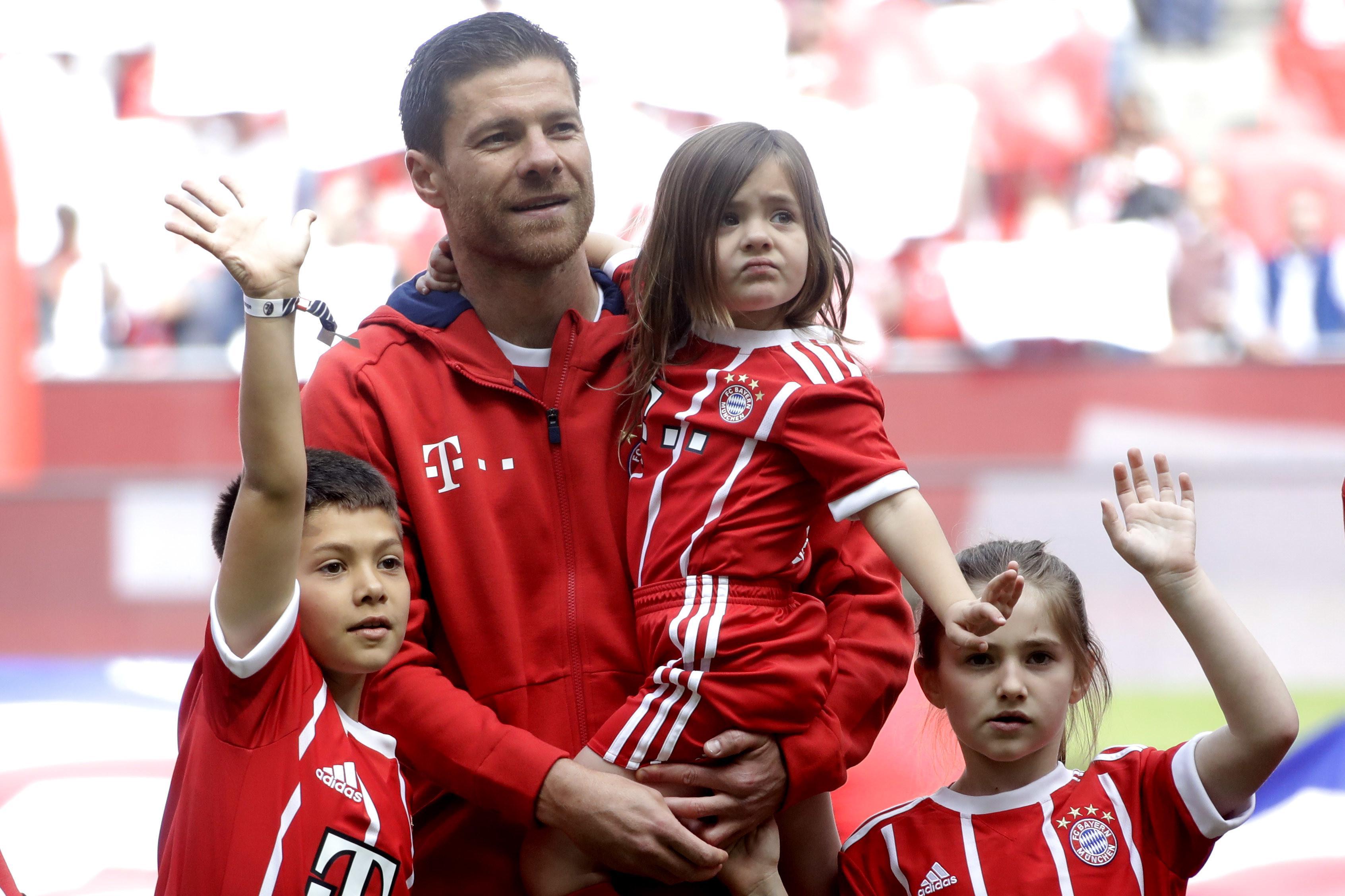 Gelandang Bayern Muenchen, Xabi Alonso, berpose bersama ketiga anaknya sebelum melakoni laga terakhir di sepak bola. Alonso dan Philipp Lahm gantung sepatu usai laga melawan Freiburg, Sabtu (20/5/2017). (AP Photo/Matthias Schrader)