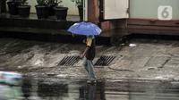 Pejalan kaki menggunakan payung saat hujan mengguyur Jakarta, Senin (26/10/2020). BPBD DKI Jakarta mengeluarkan peringatan dini cuaca berupa potensi terjadinya hujan lebat disertai petir dan angin kencang dampak dari siklon tropis Molave hingga 27 Oktober 2020. (merdeka.com/Iqbal S. Nugroho)