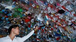 """Seorang pria melihat instalasi seni gantung sekelompok seniman yang terbuat dari sisa-sisa plastik, kaleng dan wadah di sebuah pameran """"Reduce the Litter"""" di Pusat Kebudayaan Prancis di Hanoi (15/7/2019). Pameran ini mengambil perspektif tentang produksi dan konsumsi. (AFP Photo/Nhac Nguyen)"""