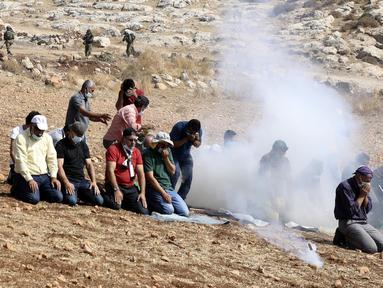 Pengunjuk rasa Palestina melaksanakan salat di tengah tembakan gas air mata tentara Israel di dekat desa Beit Dajan, Palestina (9/10/2020). Insiden terjadi ketika pengunjuk rasa menggelar aksi memprotes pencaplokan tanah yang dilakukan Israel untuk perluasan permukiman Yahudi. (AFP/Jaafar Ashtiyeh)