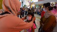 Seorang anak dipakaikan masker saat berada di Stasiun Gambir, Jakarta Pusat, Jumat (31/01). Dalam rangka pencegahan Virus Corona, PT Kereta Api Indonesia (persero) melakukan sosialisasi kepada penumpang kereta api dengan membagi-bagikan masker di stasiun Gambir. (merdeka.com/Imam Buhori)
