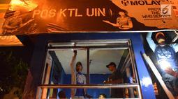 Petugas dan warga memperbaiki pos polisi yang sebelumnya dibakar massa saat peringatan Hari Buruh di Yogyakarta, Selasa (1/5) malam. Hari Buruh di Yogyakarta diwarnai aksi bakar pos polisi di pertigaan kampus UIN Sunan Kalijaga. (Liputan6.com/Gholib)