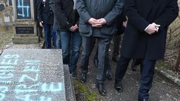 Presiden Prancis Emmanuel Macron melihat makam Yahudi yang dicoret simbol Nazi di pemakaman Yahudi, Quatzenheim, Prancis, Selasa (19/2). Macron menyatakan pelaku tidak layak menjadi warga Prancis. (Frederick FLORIN/AFP)