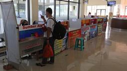 Penjaga tiket bus berbincang dengan calon penumpang di Terminal Jatijajar, Depok, Jawa Barat, Senin (6/7/2020). Terminal tipe A tersebut kembali mengoperasikan layanan bus Antar Kota Antar Provinsi (AKAP) dengan menerapkan protokol kesehatan. (Liputan6.com/Herman Zakharia)