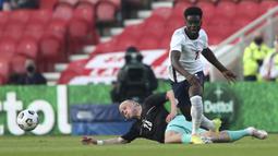 Striker Inggris, Bukayo Saka (kanan) berebut bola dengan gelandang Austria, Xaver Schlager dalam laga uji coba menjelang berlangsungnya Euro 2020 di Riverside Stadium, Middlesbrough, Rabu (2/6/2021). Inggris menang 1-0 atas Austria. (AP/Scott Heppell/Pool)