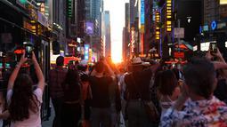 Orang-orang mengambil gambar fenomena Manhattanhenge, dimana matahari terbenam sejajar tepat dengan jalan, di 42nd street di Times Square, New York City, Kamis (12/7). Fenomena ini hanya terjadi selama beberapa hari dalam setahun. (AFP/TIMOTHY A. CLARY)