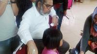 Ketua Komisi Nasional Perlindungan Anak (Komnas PA) Arist Merdeka Sirait dan bocah R yang diduga dianiaya ibu tiri. (Liputan6.com/Putu Merta Surya Putra)
