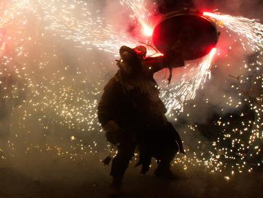 Peserta bersuka ria ambil bagian dalam festival tradisional Correfoc di Palma de Mallorca, Spanyol, Senin (21/1). Perayaan Correfocs dilakukan dengan mengenakan kostum dimana peserta mengenakan kostum iblis yang melambangkan kejahatan. (JAIME REINA/AFP)