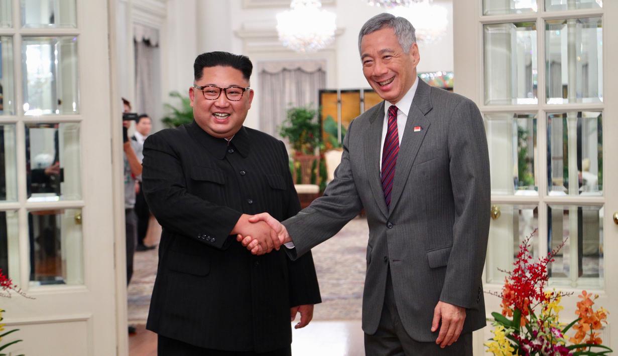 Perdana Menteri Singapura, Lee Hsien Loong bejabat tangan sambut kedatangan pemimpin Korea Utara Kim Jong-un di Istana Kepresidenan Singapura, Minggu (10/6).Kim Jong-un dan Donald Trump akan bertemu 12 Juni. (AFP Photo/HO/Kementerian Kominfo Singapura)