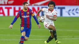 Striker Barcelona, Lionel Messi, berebut bola dengan pemain Sevilla, Jules Kounde, pada laga leg pertama semifinal Copa del Rey di Estadio Ramon Sanchez Pizjuan, Kamis (11/2/2021). Barcelona tumbang dengan skor 2-0. (AP/Angel Fernandez)