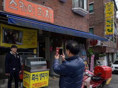 Seorang pria berpose di depan foto sutradara film Bong Joon-ho di restoran pizza bernama 'Sky Pizza' di Seoul, 13 Februari 2020. Lokasi syuting Parasite di Korea Selatan semakin ramai dikunjungi turis setelah film tersebut berhasil memboyong dan mendominasi di penghargaan Oscar 2020. (Ed JONES/AFP)