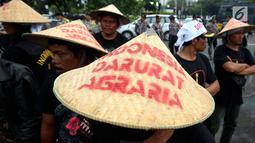 Massa tani memakai caping bertulisan 'Indonesia Darurat Agraria' menggelar unjuk rasa di depan Istana Negara, Jakarta, Rabu (27/9). Petani dari berbagai daerah menggelar unjuk rasa dalam rangka memperingati Hari Tani Nasional. (Liputan6.com/Johan Tallo)