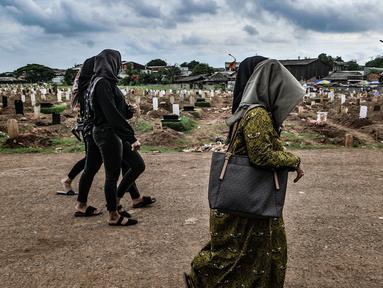 Warga berziarah ke makam anggota keluarga yang dikebumikan dengan protokol Covid-19 di TPU Tegal Alur, Jakarta, Kamis (14/1/2021). Kepala Satuan Pelaksana TPU Tegal Alur Wawan Wahyudi mengungkapkan blok pemakaman muslim khusus jenazah terpapar Covid-19 telah penuh. (merdeka.com/Iqbal S. Nugroho)