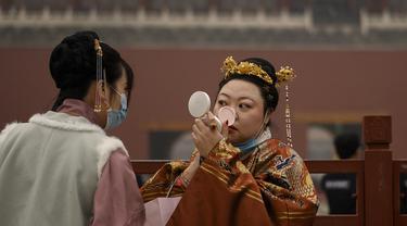 Seorang wanita dengan pakaian tradisional memeriksa riasannya saat dia berdiri di pintu masuk ke Kota Terlarang pada hari kedua Tahun Baru Imlek di Beijing (13/2/2021). Tahun Baru Imlek menandai Tahun Sapi pada 12 Februari. (AFP Photo/Noel Celis)