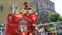 Fans Liverpool berpose dengan piala Liga Champions yang dipamerkan di Kiev, Ukraina , Kamis (24/5). Liverpool akan menghadapi Real Madrid di laga final Liga Champions. (Sergei SUPINSKY/AFP)