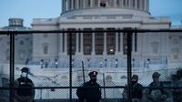 Petugas Kepolisian Capitol berjaga bersama pasukan Garda Nasional di belakang pagar pengendali kerumunan di sekitar Capitol Hill AS di Washington, Kamis (7/1/2021). Peristiwa penyerbuan di gedung Capitol Hill AS dilakukan oleh massa pendukung Donald Trump pada 6 Januari. (Brendan Smialowski/AFP)