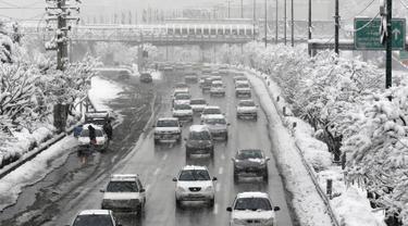 Salju tebal menutupi jalan raya di Ibu Kota Teheran, Iran, Minggu (28/1). Sekitar 20 provinsi di barat dan utara Iran terkena dampak hujan salju yang dimulai pada Kamis dan mencapai puncaknya pada Sabtu malam. (AFP PHOTO/ATTA KENALI)