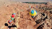 Sejumlah balon udara terbang di atas Taman Geologi Nasional Danxia di Zhangye, Provinsi Gansu, China barat laut, pada 26 Juli 2020. Sebuah festival balon udara internasional dibuka di Zhangye pada Minggu (26/7). Total 100 balon udara akan ditampilkan dalam festival tersebut. (Xinhua/Cheng Lin)
