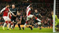 Pemain Arsenal, Danny Welbeck (tengah) mencetak gol untuk timnya ke gawang West Ham dalam lanjutan pertandingan Liga Inggris di Stadion Emirates, Minggu (22/4). Arsenal mampu unggul telak dengan skor 4-1. (AP/Alastair Grant)