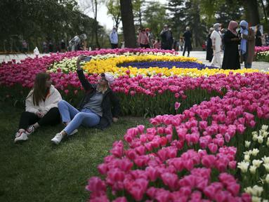 "Orang-orang mengunjungi ladang tulip mekar di Taman Emirgan di Istanbul sehari sebelum ""penguncian penuh"" atau lockdown, Rabu (28/4/2021). Turki akan memberlakukan lockdown penuh selama tiga minggu dari 29 April hingga 17 Mei 2021 untuk membendung penyebaran virus corona. (AP Photo/Emrah Gurel)"