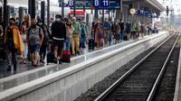 Penumpang berjalan di sepanjang peron di stasiun kereta utama di Frankfurt, Jerman, Jumat (14/8/2020). Mengenakan masker untuk melindungi diri dari corona Covid-19 adalah kewajiban di transportasi umum di Jerman. (AP Photo/Michael Probst)