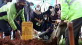 Istri mantan penggawa Timnas Indonesia Ricky Yacobi, Harly Ramayani (duduk tengah) menyaksikan proses pemakaman suaminya di TPU Tanah Kusir, Jakarta, Sabtu (21/11/2020). Ricky Yacobi meninggal dunia pada Sabtu (21/11) akibat serangan jantung pada usia 57 tahun. (Liputan6.com/Helmi Fithriansyah)