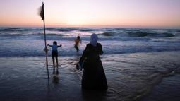 Orang Arab Israel menikmati laut Mediterania selama liburan Idul Fitri, di Tel Aviv, Israel (25/5/2020). Idul Fitri menandai akhir bulan suci Ramadhan, perayaan tiga hari yang biasanya menggembirakan telah berkurang secara signifikan karena pandemi coronavirus.  (AP Photo/Oded Balilty)