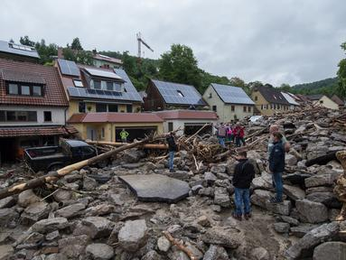 Warga saat memeriksa lokasi tempat tinggal mereka pasca luapan banjir di wilayah Braunsbach, Jerman selatan (30/5). Banjir membawa beragam material lumpur bercampur batu serta ranting hingga batang pohon. (Marijan Murat / dpa / AFP)