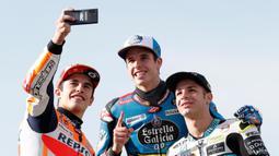 Pembalap MotoGP Marc Marquez (kiri) bersama pembalap Moto2 Alex Marquez (tengah) dan pembalap Moto3 Lorenzo Dalla Porta (kanan) berswafoto di depan Valencia Motorcycle Grand Prix, Spanyol, Minggu (17/11/2019). Ketiganya sukses merebut gelar juara dunia tahun 2019. (AP Photo/Alberto Saiz)