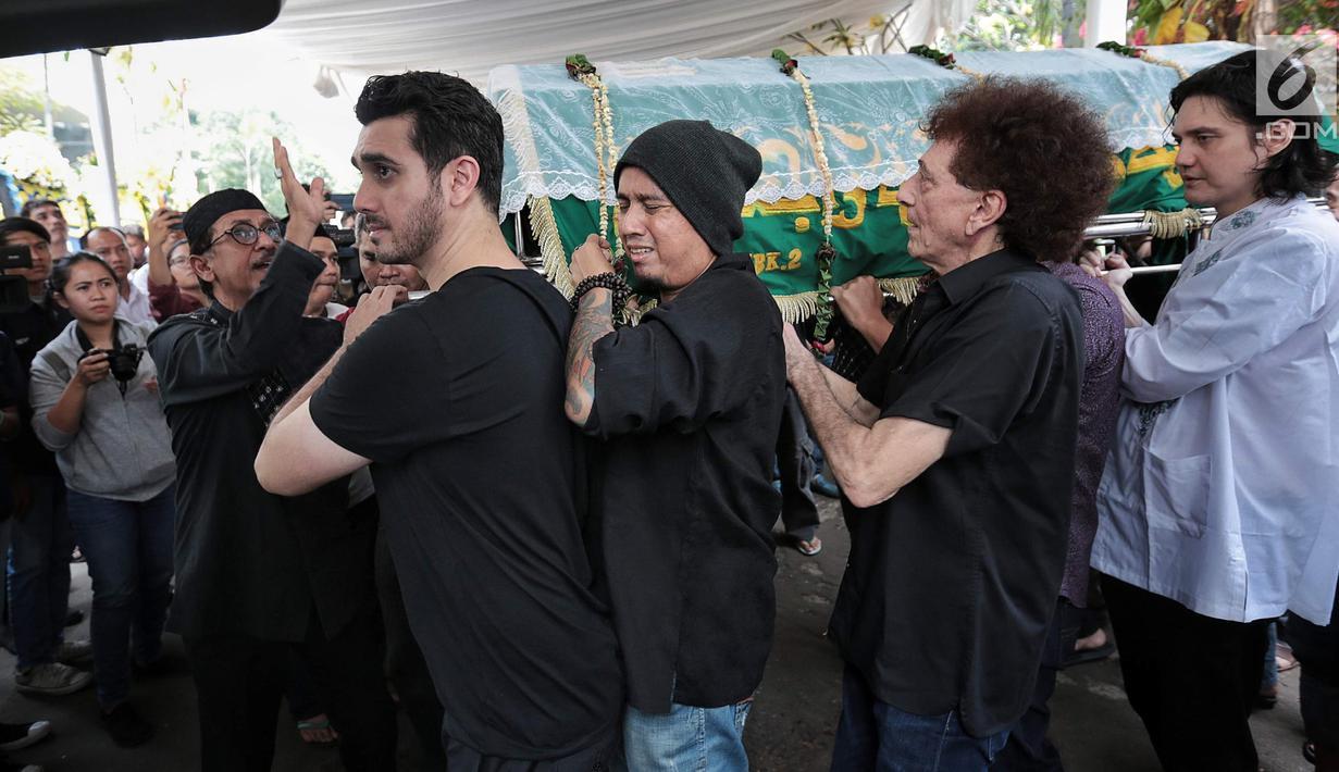 Fachri Albar (kiri) bersama Achmad Albar (dua kanan) dan para kerabat membawa jenazah Faldy Albar untuk disalatkan di Cinere, Depok, Jawa Barat, Kamis (30/8). Faldy Albar merupakan putra ketiga Ahmad Albar. (Liputan6.com/Faizal Fanani)