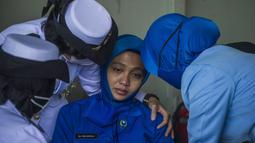 Personel militer menghibur awak KRI Nanggala 402 saat menggelar Tabur Bunga dari geladak Helly KRI Dr Soeharso-990 di perairan utara pulau Bali, Jumat (30/4/2021). Kegiatan tabur bunga digelar sebagai penghormatan terahir bagi awak KRI Nanggala 402 yang gugur dalam medan tugas. (Juni Kriswanto/AFP)