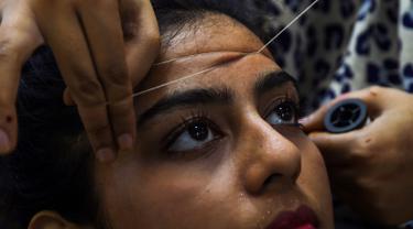 Seorang wanita Pakistan membersihkan rambut di wajah di salon kecantikan menjelang  Hari Raya Idul Fitri di Karachi (3/6/2019). Umat Muslim di seluruh dunia sedang bersiap untuk merayakan Hari Raya Idul Fitri, yang menandai akhir bulan puasa Ramadan. (AFP Photo/Asif Hassan)