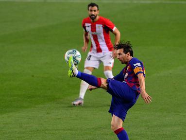 Penyerang Barcelona, Lionel Messi berusaha mengontrol bola saat bertanding melawan Athletic Bilbao pada lanjutan La Liga Spanyol  di stadion Camp Nou, Barcelona (23/6/2020). Barcelona menang tipis atas Bilbao 1-0 berkat gol tunggal Ivan Rakitic. (AFP/Pau Barrena)