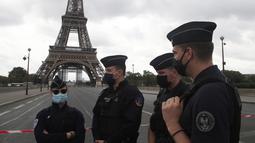 Petugas polisi Prancis mengamankan jembatan menuju Menara Eiffel di Paris, Rabu (23/9/2020). Polisi Paris telah memblokir daerah sekitar Menara Eiffel setelah ancaman bom telepon. (AP Photo / Michel Euler)