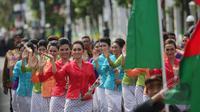 """Sejumlah mojang Bandung mengenakan pakaian tradisional sunda melambai-lambaikan tangan saat melakukan """"Historical Walk"""" dalam peringatan ke-60 tahun Konferensi Asia Afrika di jalan Asia Afrika, Bandung, Jumat, (24/4/2015).  (Liputan6.com/Herman Zakharia)"""