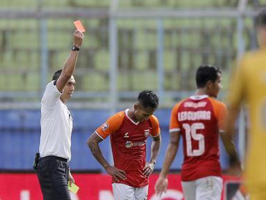 Pemain Borneo FC Samarinda, Hendro Siswanto, menerima kartu merah dari wasit, Fariq Hitaba, setelah melanggar pemain Bhayangkara Solo FC, TM Ichsan, dalam pertandingan Babak Penyisihan Grup B Piala Menpora 2021 di Stadion Kanjuruhan, Malang. Senin (22/3/2021). (Bola.com/Arief Bagus)