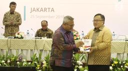 Ketua KPU Arief Budiman memberikan cenderamata kepada Menteri PPN/Bappenas Bambang Brodjonegoro saat Penyampaian Rancangan Teknokratik RPJMN 2020-2025 di Gedung KPU, Jakarta, Selasa (25/9). (Liputan6.com/Herman Zakharia)