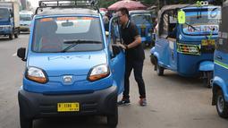 Penumpang naik angkutan umum Qute di kawasan Kota, Jakarta, Senin (24/7). Sebanyak 17 unit Angkutan Pengganti Bemo (APB) tersebut mampu mengangkut tiga penumpang dan mulai diuji coba untuk mengetahui kelayakan armada. (Liputan6.com/Immanuel Antonius)