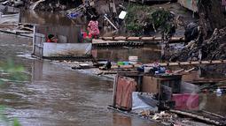 Masih banyak warga bantaran kali Ciliwung Jakarta yang memanfaatkan air kali untuk kehidupan sehari - hari. Tampak beberapa warga memanfaatkan air kali Ciliwung sebagai tempat Mandi Cuci Kakus (MCK), Jakarta, Jumat (20/2/2015). (Liputan6.com/JohanTallo)